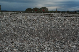 Tugnet Ice House: three curve roofed bunkers next to a pebble beach