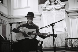 Jandek playing an acoustic guitar and wearing a hat