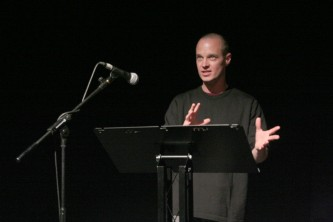 Craig Dworkin standing by a microphone