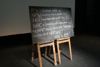 A blackboard with text in front of a screen
