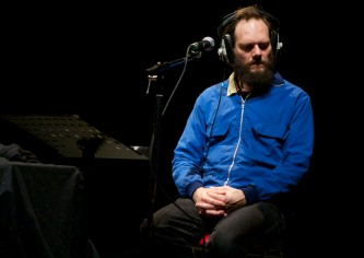 A man in a blue jacket seems to listen intently whilst wearing large headphones