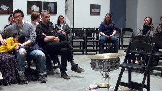 A small audience looking at sean meehan's percussion and chair with no sean