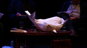 two white whales made of paper perch on a low coffee table