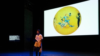 Nisha on stage with glowing screen of a yellow circle with a blue figure drawing