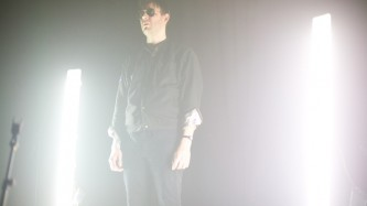 A man in sunglasses stares despondently lit by two very bright vertical lights
