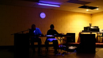By blacklight in front of a yellow wall two silhouetted people perform