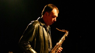 John Butcher holds and plays a saxophone