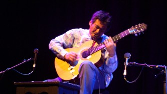 Kazuo Imai playing an acoustic guitar on stage at MLFC 05