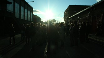 The sun low in the sky above Easterhouse, an audience at a performance