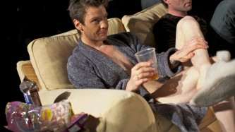 Man in a dressing gown and foundation sits on a beige sofa