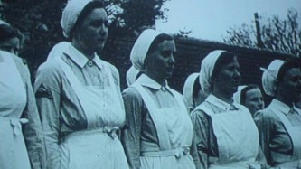 A row of people in uniforms, pinafores, hats