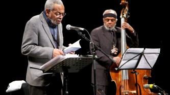 Amiri Baraka reads poetry at a mic and Henry Grimes plays a double bass bass