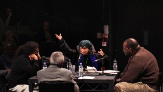 Three folks sit around a table looking at Sonia Sanchez as she gesticulates