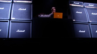 Ryoji Ikeda operating a laptop surrounded by amplifiers