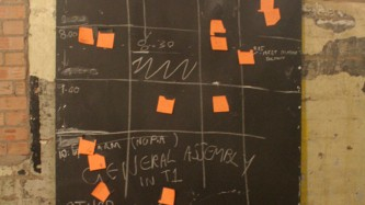 A blackboard with chalk lined box shapes and orange post-it notes by a wall