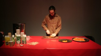 a man stands behind a red table