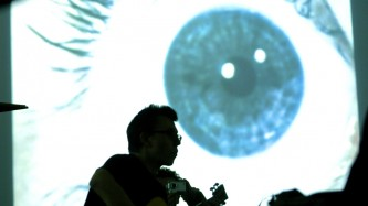 Burkhard Stangl silhouetted against a projection of an eye