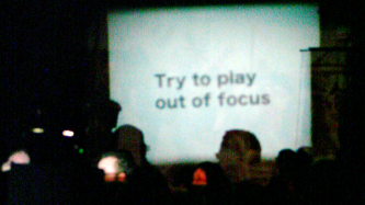 """A blurry projection screen has the words """"Try to play out of focus"""""""