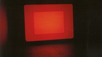at the end of a dark gallery a screen throbs with layers rectangles of red