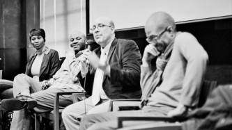 A panel of four folks sit as one wearing a dark jacket and specs speaks