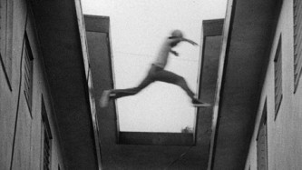 B&W film still of a boy jumping from one roof to another, taken from below