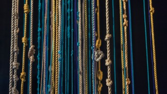 Tens of silken knotted ropes in shades of gold and blue hang vertically