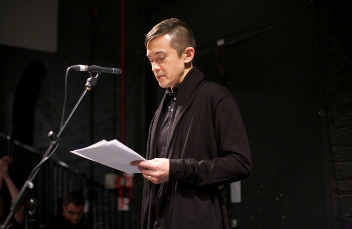 Eugene Thacker in black reading from a paper against a dark background