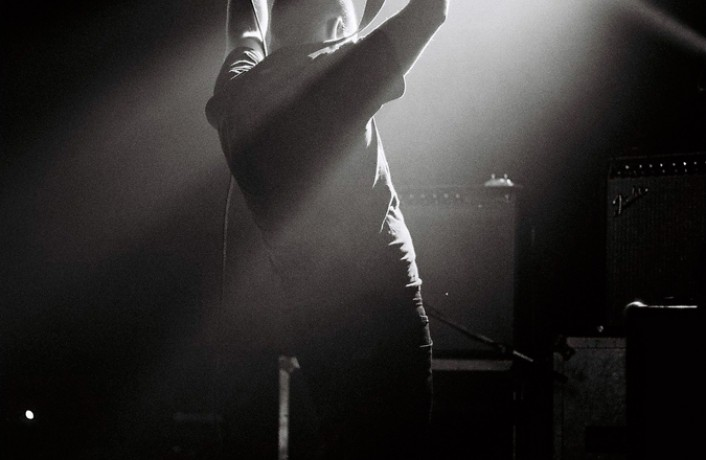 A man holding a flying v guitar above his head