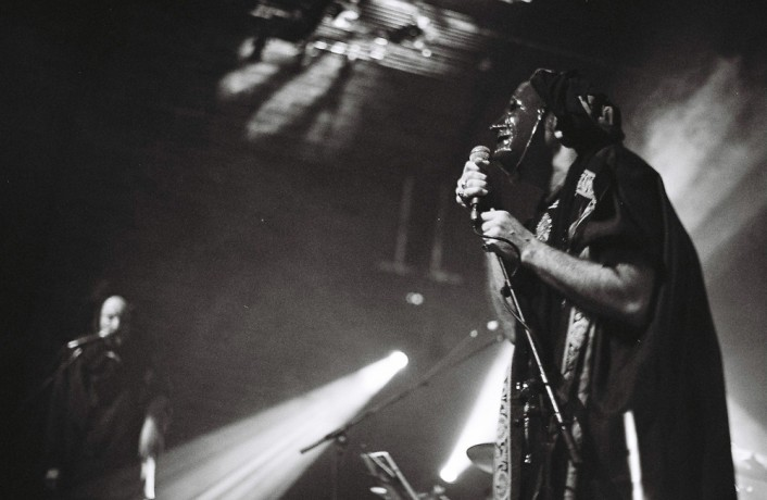 A masked figure holds a microphone in stark lighting