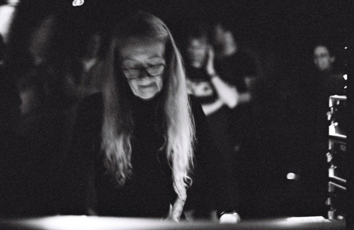 Maryanne Amacher operating a mixing console, wearing glasses