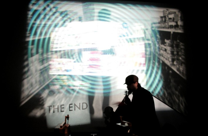 A man in front of a multi layered projection, a sign saying 'the end'
