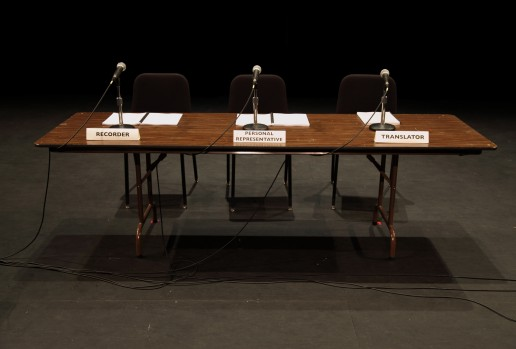 A table with three microphones, chairs and named placards. The seats are empty