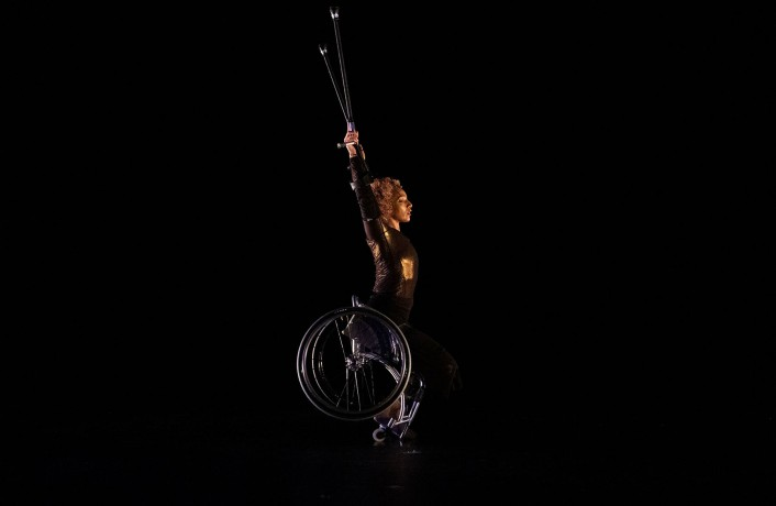 Alice is centre stage in her manual wheelchair, arms raised, crutches extended