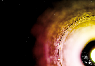 yellow pink and white circular form on right of image against black background