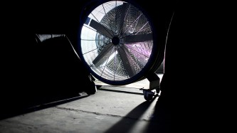 A large industrial fan is backlit