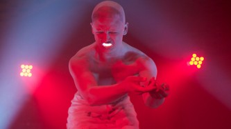 a figure bathed in red writhes as they perform with a red light in their mouth