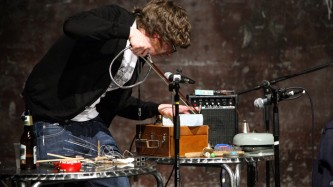 Ali Robertson Hunches over a table with lots of small metal objects on it