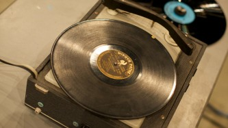 A record deck with an old record on another record with a blue label to the side