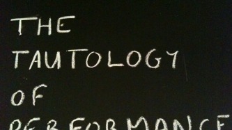 """""""The Tautology of Performance"""" written on a board in chalk"""