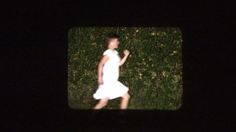 A woman in a white dress jogs across a frame screened on a wall