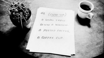 A cactus and coffee cup and a sheet of paper sit on a table