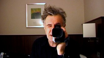 A man looks through camcorder viewfinder in the reflection in a mirror