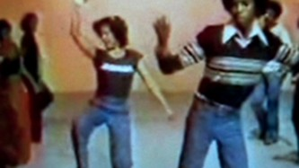 A video still of several folks pulling dance moves in front of an orange wall