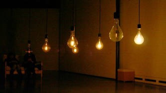 A series of large dimly lit light bulbs hanging in a room
