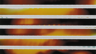 Strips of 16mm laid horizontally to show red and yellow flares of light
