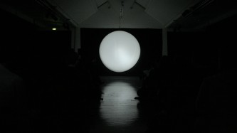 A large white circular form hovers in the mid distance at the end of a long room