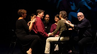 John is sitting on the stage, surrounded by people, all touching each other