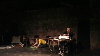 Three men operating electronic equipment. Fraser is in yellow on the floor