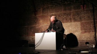 Rolf Julius leans forward over a large white box and mixer and performs