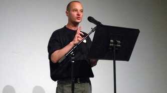 Craig Dworkin standing by a microphone giving a talk